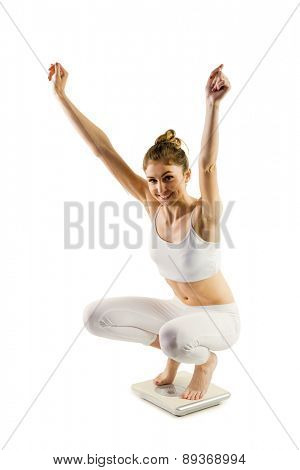 Slim woman cheering on scales on white background