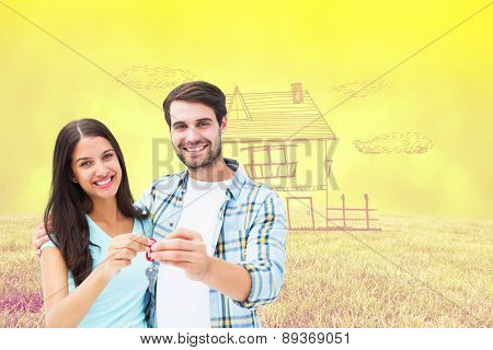 Happy young couple showing new house key against field against glowing lights