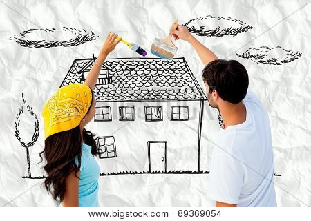 Happy young couple painting together against crumpled white page