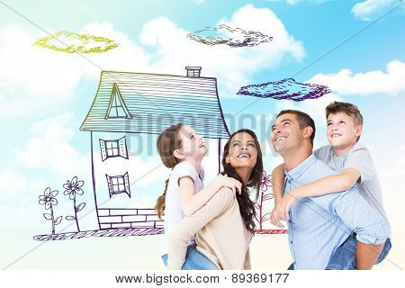Parents giving piggyback ride to children while looking up against blue sky