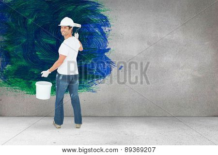 Happy man using paint roller against grey room
