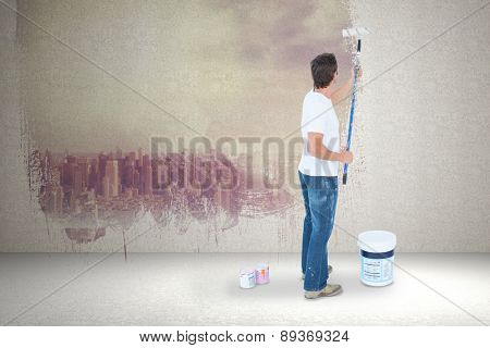 Man painting on white background against room with large window looking on city