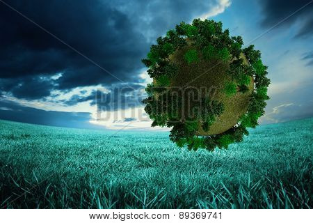 Sphere covered with forest against blue sky over green field