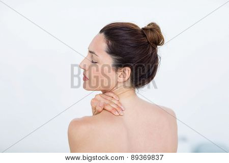 Woman touching her shoulder in medical office