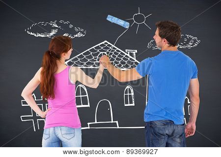 Couple painting a wall together against black background