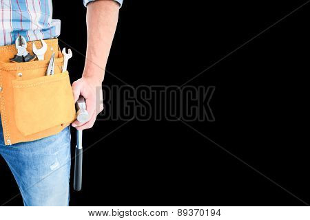 Handyman wearing tool belt while holding hammer against black