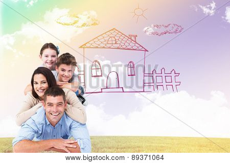 Family lying on top of each other against blue sky over green field