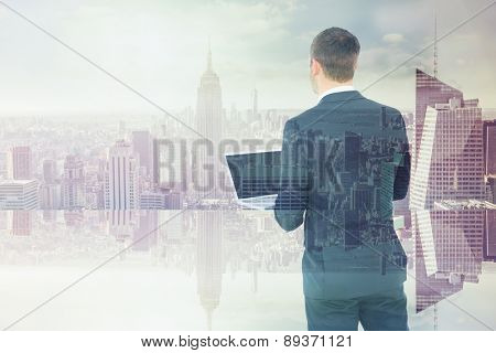 Businessman looking up holding laptop against room with large window looking on city