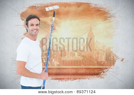 Happy man using paint roller against sun shining over city