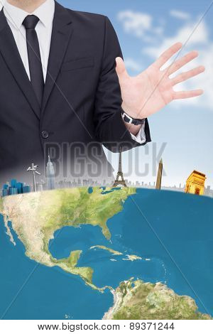 Businessman standing with hands spread out against blue sky