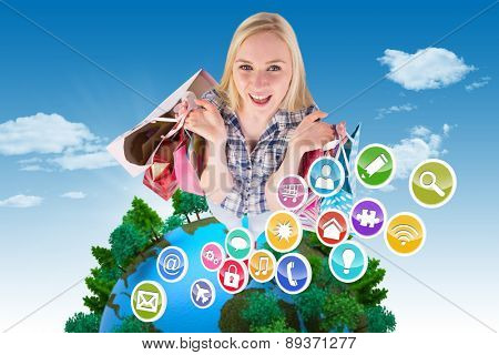 Pretty young blonde holding shopping bags against blue sky