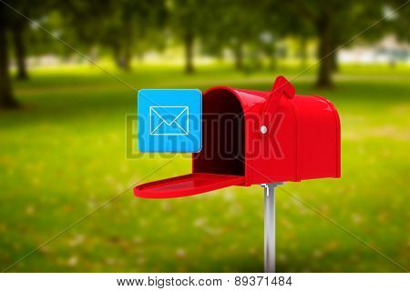 Red email postbox against park