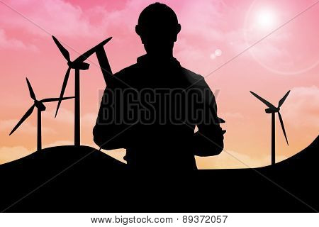 Portrait of smiling manual worker holding various tools against sky and mountains