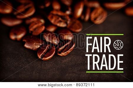 fair trade against dark blurred coffee seeds laid out together on a black table