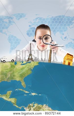 Businesswoman typing and looking through magnifying glass against background with hexagons and world map