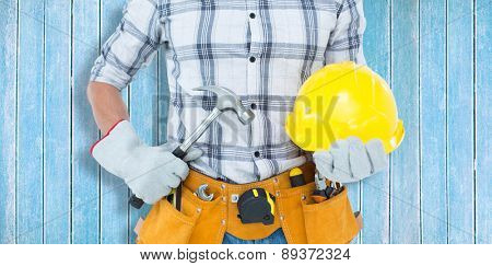 Handyman holding hammer and hard hat against wooden planks