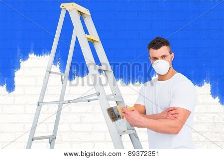 handyman with paintbrush and ladder against white wall