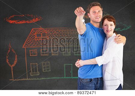 Couple holding keys to home against black wall