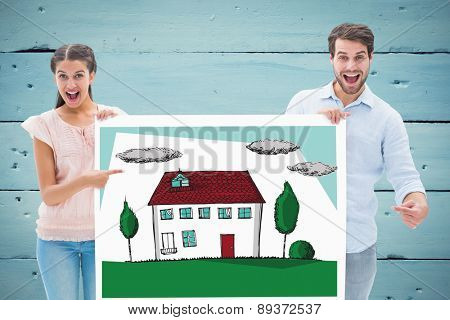 Attractive young couple smiling at camera holding poster against painted blue wooden planks