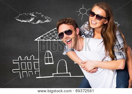 Smiling young man carrying woman against black wall