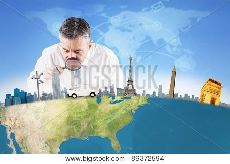 Mature businessman examining with magnifying glass against futuristic technology interface