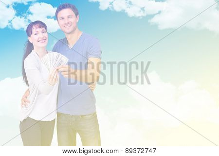 Couple holding fan of cash against blue sky