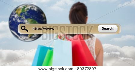 Rear view of brunette holding shopping bags against cloudy sky