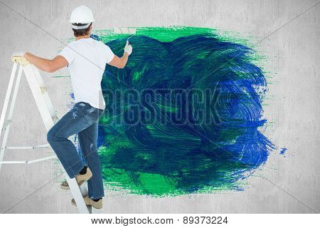Man on ladder painting with roller against white and grey background
