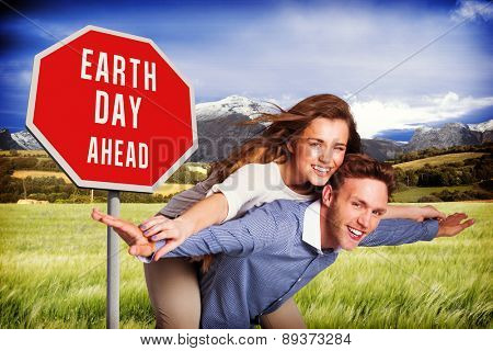 Smiling young man carrying woman against scenic backdrop
