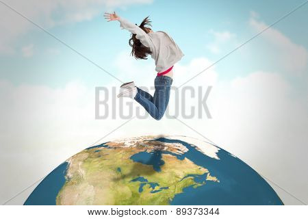 Cheerful young woman jumping against blue sky