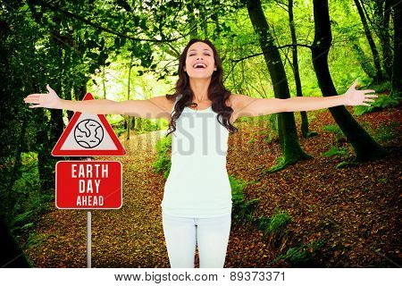 Carefree brunette with arms out against peaceful autumn scene in forest