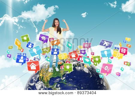 Happy casual woman cheering at camera against blue sky