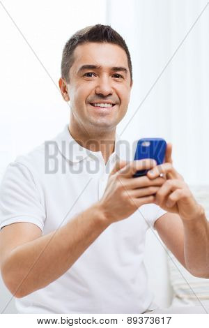 technology, people, lifestyle and communication concept - happy man with smartphone at home