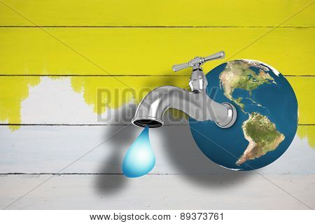 Earth with faucet against yellow paint on fence