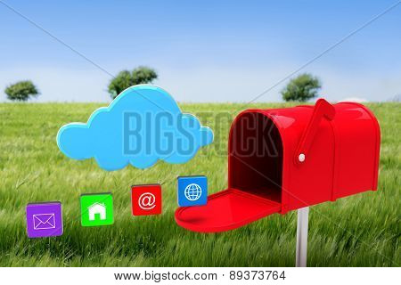 Red email postbox against green meadow