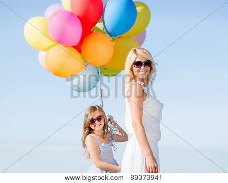 summer holidays, celebration, family, children and people concept - mother and child with colorful balloons