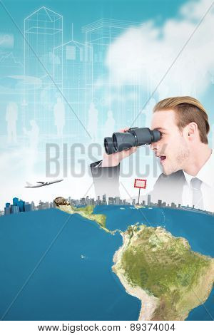 Surprised businessman looking through binoculars against blue sky