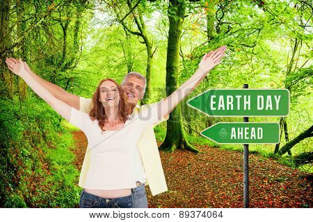 Casual couple smiling with arms raised against peaceful autumn scene in forest