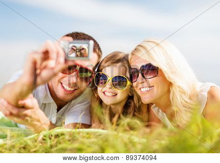 summer holidays, children and people concept - happy family with camera, blue sky and green grass taking picture