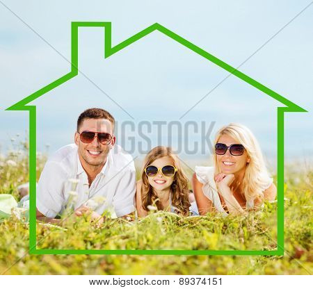home, happiness and real estate concept - happy family in sunglasses lying on a grass with house shaped illustration