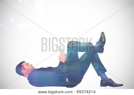 Businessman lying on the floor reading book against blurry new york street