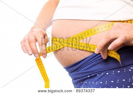 Pregnant woman measuring her bump on white background