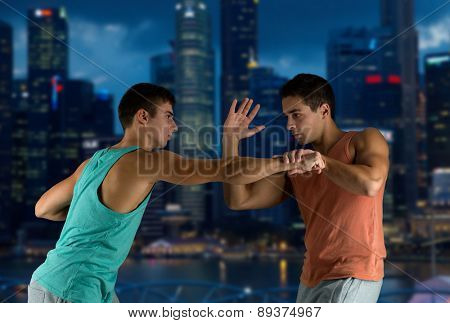 sport, competition, strength and people concept - young men fighting hand-to-hand over night city background