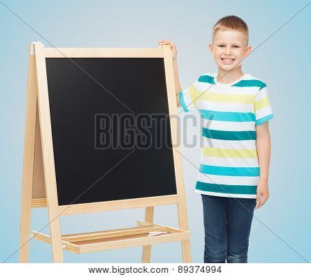 people, school, children, advertisement and education concept - happy little boy with blank blackboard over blue background
