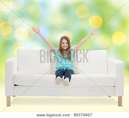 home, leisure, people and happiness concept - smiling little girl sitting with raised hands on sofa over green lights background