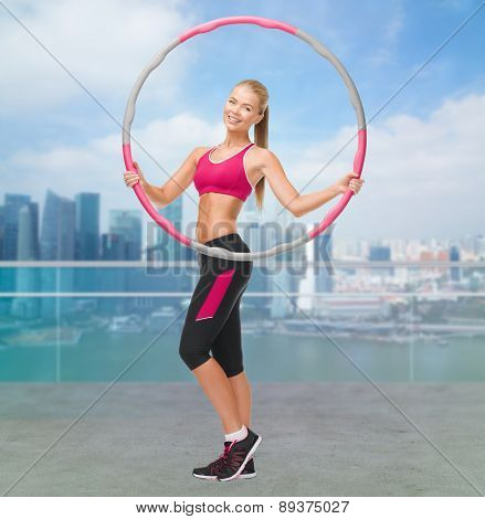 fitness, sport, people and healthcare concept - young sporty woman exercising with hula hoop over city waterside background