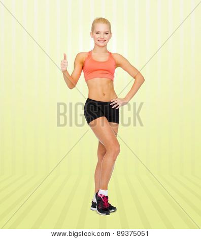 fitness, sport, gesture and weight loss people concept - beautiful athletic woman in sportswear showing thumbs up over yellow striped background