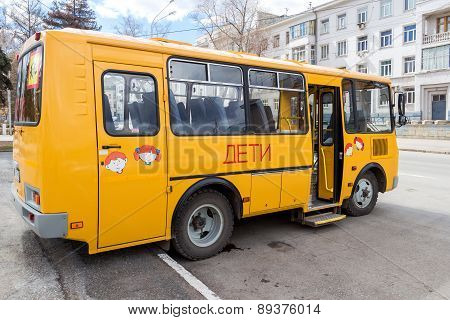 Public School Bus Parked Up In The Street Wait To Collect School Children. Text On Russian: