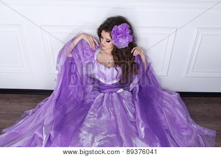 Beautiful Brunette Woman Wearing In Purple Dress Leaning On Modern Wall, Model Posing