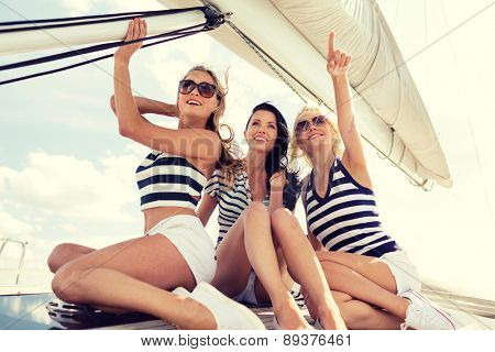 vacation, travel, sea, friendship and people concept - smiling girlfriends sitting on yacht deck